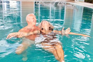 Mann hilft seiner Frau beim Schwimmen