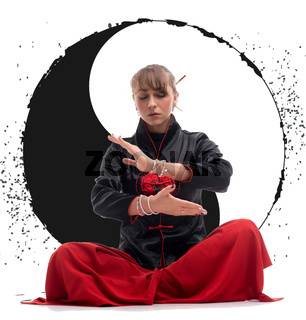 Woman practicing wushu on the floor with Yin Yang sign
