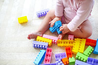 Cute toddler girl having fun with toy blocks sitting on the carpet