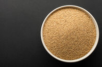 amaranth seeds in ceramic bowl isolated on dark background. top view