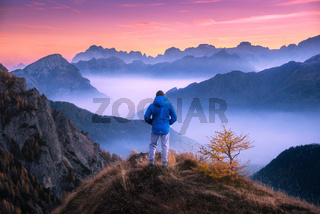 Man looking on mountain valley with low clouds at colorful sunset