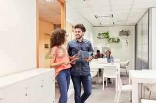 Zwei junge Kollegen arbeiten zusammen im Büro