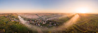 Aerial view of traditional Ukrainian village at sunset. Wide angle panoramic landscape of rural area. Early autumn. Smoke spreads through the village. Ripchytsi village, Ukraine