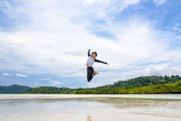 Happy asian woman jumping fun on the beach