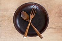 Wooden plate with spoon and fork on wooden background
