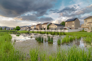 Overcast sky over a scenic neighborhood with multi storey homes and shiny pond