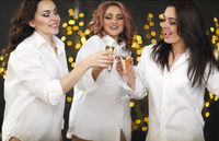 Smiling women with glasses of champagne over lights background