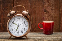 retro alarm clock and a cup of coffee on arustic barn wood
