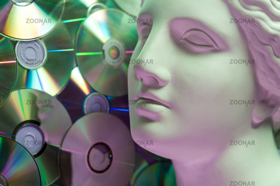 Antique statue of Venus head close up on a glitter CDs background. Concept of music, style, vintage.