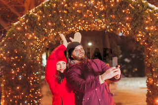 Couple making selfie having fun at Christmas evening