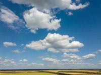 Panoramic landscape with beautiful white clouds and fields on a background of blue sky in a sunny day. Aerial view frome drone,