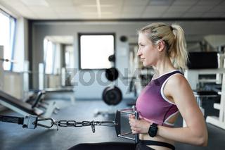 Junge Frau beim Rückentraining am Seilzug