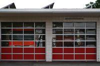 Feuerwehrwagen hinter Garagen