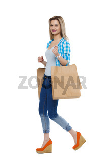 Side view of going  woman  with shopping bags . beautiful girl in motion.
