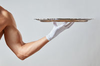 Muscular hand of waiter in a white glove holding a silver vintage empty tray on a white background.