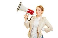 Geschäftsfrau mit Megafon stellt Forderung