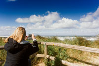 Woman is taking a snapshot of the beach the sea and the dunes