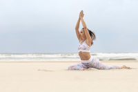 Young sporty slim woman doing yoga exercise on sand of the tropical sea beach