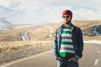 Portrait of a thoughtful stylish hipster with a beard in sunglasses and a hat with a backpack on the background of the snow-capped Mount Elbrus in the Caucasus at sunset