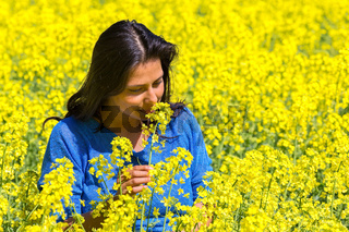 Woman smells flower in yellow rapeseed field