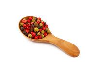 Wooden scoop spoon full of mixed peppercorns