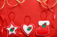 Handmade rustic Christmas tree decorations on red felt background