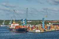 Port crane loads a container on Pier for transportation of import export and business logistic in Fredericia Denmark.