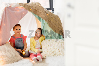 girls with book and torch in kids tent at home