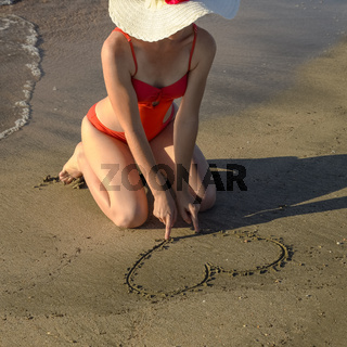 girl in a white hat and in a red swimsuit draws a heart on the beach sand.