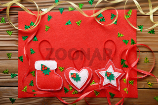 Handmade rustic Christmas tree decorations with red felt on wooden table