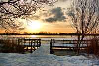 Bright sunrise at the jetty near the lake on a snowy winter morning