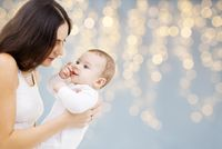 mother with baby over festive lights background