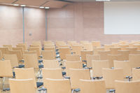 Empty wooden seats in a cotmporary lecture hall.
