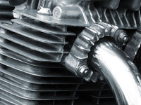 the engine block of an old vintage motorcycle with black frame and shiny chrome exhaust pipes