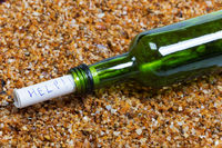 Bottle of wine with help message on wet beach