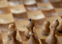 Carved wooden chessmen with focus on king