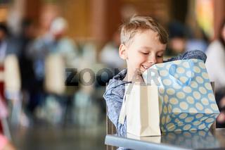 Junge schaut in eine Einkaufstüte
