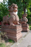 Two large lion stone statues in a buddhist temple