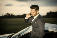 Handsome young man by his car with cell phone
