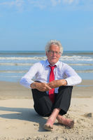 Business man sitting at the beach