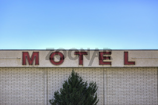 Motel sign with sky and tree
