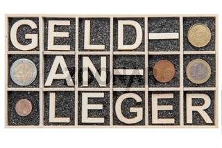 Wooden letters word GELDANLEGER coins