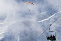 Chairlift and paraplane on ski resort at cold winter day