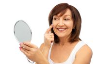 portrait of smiling senior woman with mirror