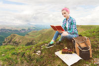 A traveler girl sits in the mountains on the grass and reads a book on the background of epic mountains. The concept of reading during rest and vacations