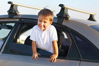 Portrait of a smiling little boy at beach in the car