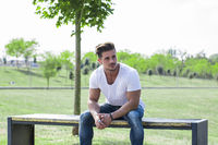 Attractive muscular man in city park looking away