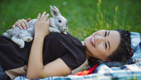 Beautiful Mature Asian Woman is Laying on Ground and Hugging a Rabbit