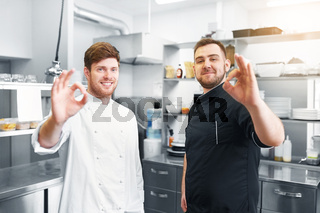 happy chefs at restaurant kitchen showing ok sign