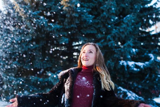 Enjoying the snowfall under the fir tree
